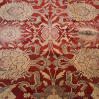 A Large Early Agra Carpet with an allover design upon a red and cream ground within multiple borders. Hammer: £18,500