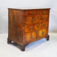 A George II Walnut Chest The Herringbone Inlaid Top above two short and three long drawers with brass handles and escutcheons, raised upon bracket feet, Hmmer £980