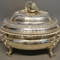 A George III Silver Soup Tureen, the cover mounted with an opening pomegranate above a two handled tureen with four scroll feet bearing engraved crest Hammer £4,800